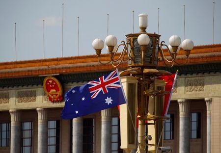 An Australian national flag flutters next to a Chinese national flag in front of the Great Hall of the People at the Tiananmen Square during Australian Prime Minister Julia Gillard's visit to Beijing