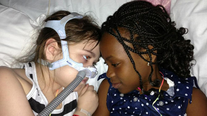 In this May 30, 2013 photo provided by the Murnaghan family, Sarah Murnaghan, left, lies in her hospital bed next to adopted sister Ella on the 100th day of her stay in Children's Hospital of Philadelphia. The 10-year-old suburban Philadelphia girl has been hospitalized at Children's Hospital of Philadelphia for three months with end-stage cystic fibrosis. Her family wants an exception made for Sarah to get an adult lung, because so few pediatric lungs become available. Kathleen Sebelius, U.S. Secretary of Health and Human Services, says she doesn't want to intervene in transplant decisions when other children are just as sick. Sarah's relatives say they want the policy changed for all children awaiting a lung transplant, not just Sarah. (AP Photo/Murnaghan family)