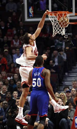 Chicago Bulls center Joakim Noah (13) dunks past Philadelphia 76ers forward Lavoy Allen (50) during the first half of an NBA basketball game, Thursday, Feb. 28, 2013, in Chicago. (AP Photo/Charles Rex Arbogast)