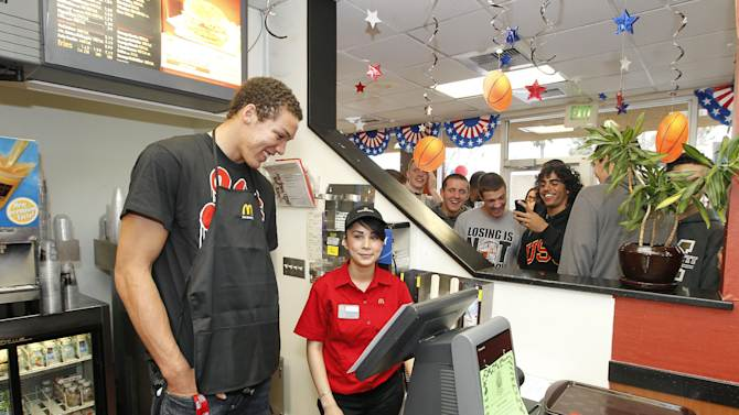 McDonald's All American Games player Aaron Gordon, left, from Archbishop Mitty High School, helps out behind the counter with employee Daisy Partida, right, during a send-off event prior to the All American Games in Chicago on April 3. The celebration was held at a McDonald's restaurant on Tuesday, March 19, 2013, in San Jose, Calif.  Three other student athletes from the Bay Area were selected among 800 nominees to participate in McDonald's All American Games. The elite list of prep school stand outs has included Michael Jordan, Kobe Bryant and LeBron James. (Photo by Tony Avelar/Invision for McDonald's/AP Images)