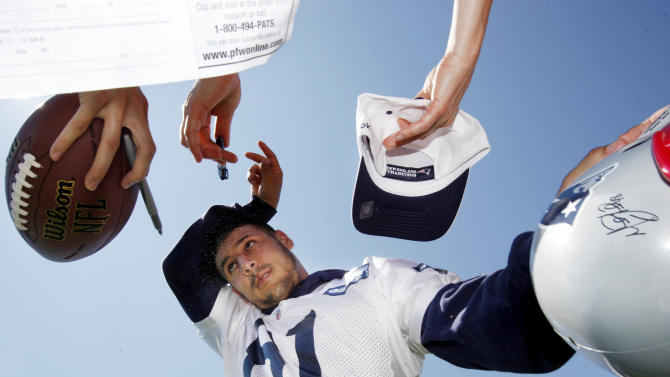 New England Patriots tight end Aaron Hernandez wipes his brow while signing autographs after an NFL football training camp in Foxborough, Mass., Sunday, July 31, 2011. (AP Photo/Michael Dwyer)