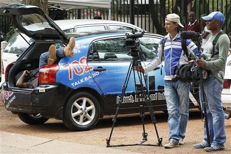 Journalists wait outside Pretoria's Brooklyn police station where Oscar Pistorius is supposed to report as part of his bail conditions