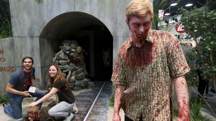 "People have their photo taken next to a man dressed as a zombie at a booth for ""The Walking Dead"" during the 2014 Comic-Con International Convention in San Diego"