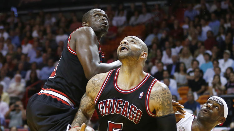 Miami Heat's LeBron James (6) along with Chicago Bulls players Carlos Boozer (5) and Luoi Deng (9)  watch as James scores two points  during the first half of a NBA basketball game in Miami, Friday, Jan. 4, 2013. (AP Photo/J Pat Carter)