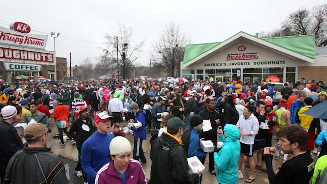 Thousands eat their doughnuts outside the Krispy Kreme during the Krispy Kreme Challenge Saturday Feb. 5, 2011, at the Krispy Kreme on North Person St. in Raleigh, N.C. About 7,500 people were scheduled to take place in the annual run. The rules are simple and stomach-churning: run for two miles, eat a dozen Krispy Kreme doughnuts and then run back along the same two miles. (AP Photo/The News & Observer, Ethan Hyman) MANDATORY CREDIT