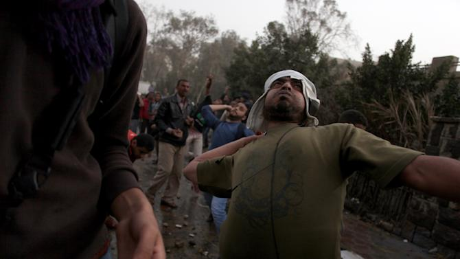 An Egyptian protester throws a stone during clashes between supporters and opponents and supporters of Egypt's powerful Muslim Brotherhood near the Islamist group's Cairo, Egypt headquarters Friday, March 22, 2013. (AP Photo/Khalil Hamra)