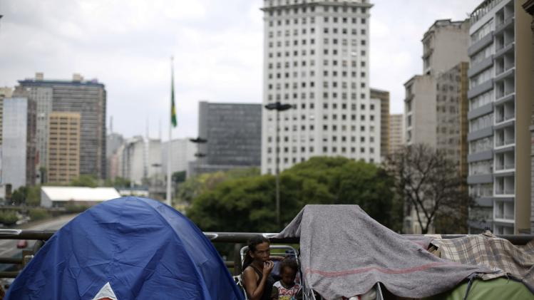 A girl and her mother, members of Roofless Movement, eat in between rows of tents on the Cha viaduct in front of the city hall of Sao Paulo
