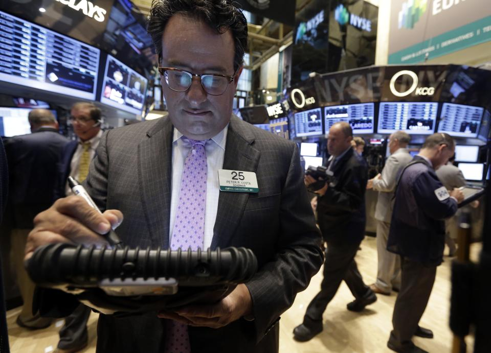 Trader Peter Costa, left, works on the floor of the New York Stock Exchange Wednesday, Sept. 18, 2013. Stocks were little changed in early trading Wednesday as investors wait to hear from the Federal Reserve on the fate of the central bank's bond-buying program. (AP Photo/Richard Drew)