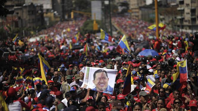 Supporters of Venezuela's late President Hugo Chavez walk behind his coffin as it is paraded through the street from the hospital, where he died on Tuesday, to a military academy in Caracas, Venezuela, Wednesday, March 6, 2013. Seven days of mourning were declared, all schools were suspended for the week and friendly heads of state were expected for an elaborate funeral Friday. (AP Photo/Rodrigo Abd)