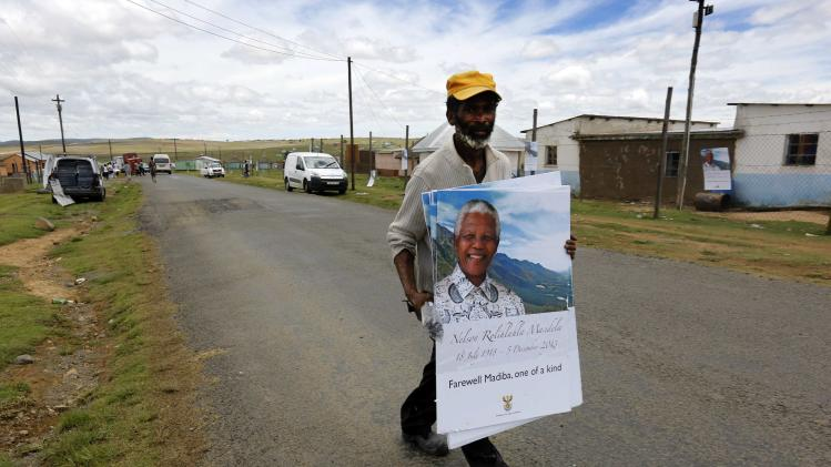 A man carries posters of former South African President Mandela through the perimeter of Mandela's property in Qunu