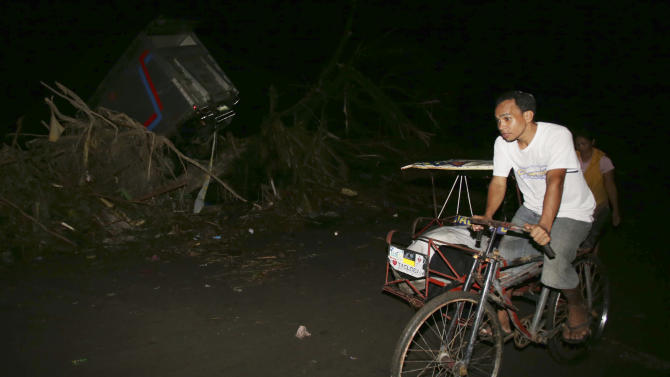 Survivor Sandy Torotoro pedals his pedicab along a dark street after powerful Typhoon Haiyan slammed into Tacloban city, Leyte province central Philippines on Saturday, Nov. 9, 2013. The 44 year-old bicycle taxi driver who lives near an airport with his wife and 8 year-old daughter, said he and others took refuge inside a parked Jeep to protect themselves from the storm, but the vehicle was swept away by a surging wall of water. (AP Photo/Aaron Favila)