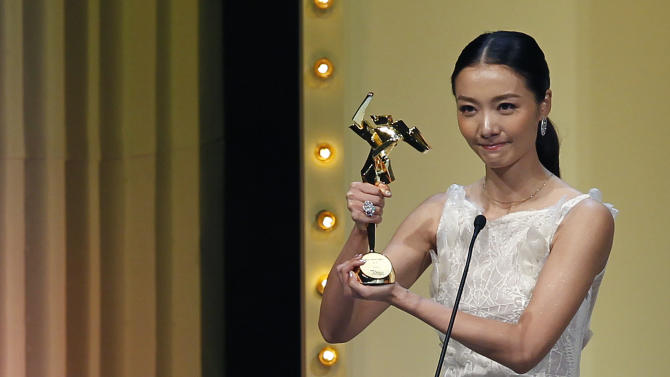"""Chinese actress Qi Xi gestures after she receives the Best Newcomer award for the film """" Mystery """"at the Asian Film Awards in Hong Kong Monday, March 18, 2013. (AP Photo/Vincent Yu)"""