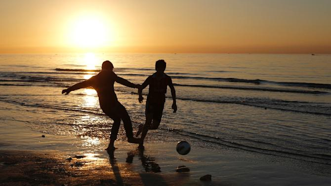 Palestinians play football on a beach as the sun sets over Gaza City, on January 21, 2015