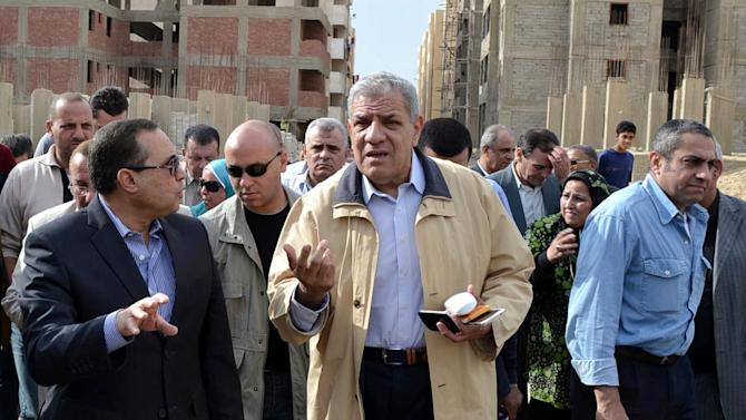 FILE - In this Nov. 24, 2013 file photo, Ibrahim Mehlib, center, tours a government housing project in Ismailiya, Egypt. On Sunday, Feb. 2, 2014, Egypt's new Prime Minister Ibrahim Mehlib urged a halt to protests and strikes to give the nation a breather to rebuild after more than three years of deadly turmoil, a call made by his predecessors to no avail. The turmoil sweeping Egypt since the 2011 ouster of Hosni Mubarak has devastated the economy, particularly the vital tourism sector. (AP Photo/Khaled Kandil, File)