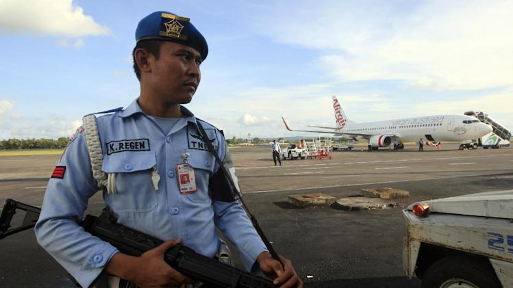 CORRECTS YEAR - An Indonesian Air Force member stands guard near a Virgin Australia airplane in Bali, Indonesia, Friday, April 25, 2014. A drunken passenger who caused a hijack scare on a Virgin Australia flight by trying to break into the cockpit was arrested Friday after the plane landed on Indonesia's resort island of Bali, officials said. (AP Photo/Firdia Lisnawati)