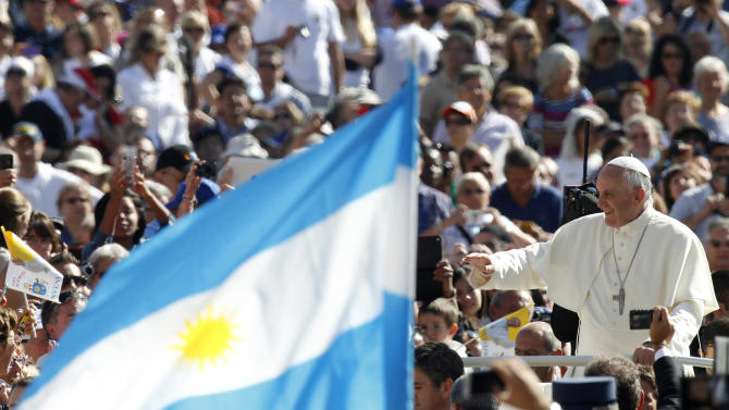 Pope Francis waves to faithful as he arrives for his weekly general audience in St. Peter's Square at the Vatican, Wednesday, Sept. 18, 2013. At left, a faithful waves an Argentine flag. (AP Photo/Riccardo De Luca)