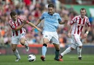 Stoke City's Michael Owen (L) fights for the ball with Manchester City's Javi Garcia (C) during the Premiership football match at The Brittania Stadium in Stoke. The game ended 1-1