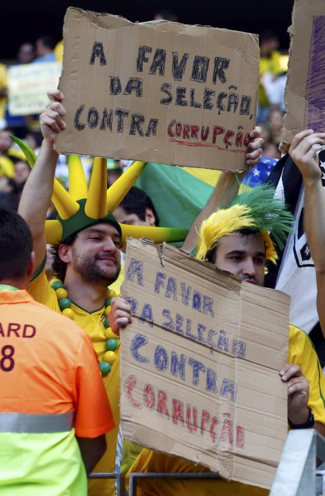 Protesters hold up signs before the Confederations Cup Group A soccer match between Brazil and Mexico at the Estadio Castelao in Fortaleza