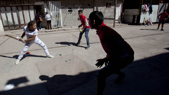 Caacupe cricket team Milagros Mendez, left, bats during a training session at the Villa 21-24 slum in Buenos Aires, Argentina, Saturday, March 22, 2014. The International Cricket Council has recognized the team, formed from the children of the Villa 21-24 shantytown, honoring them as a global example for expanding the sport, which in certain countries, like India, is widely played, but in many parts of the world restricted to elite sectors of society. Introducing cricket in the slum began in 2009 as an idea to transform the game into a social integration mechanism, before that it rarely breached the gates of the country's upscale private schools. (AP Photo/Natacha Pisarenko)