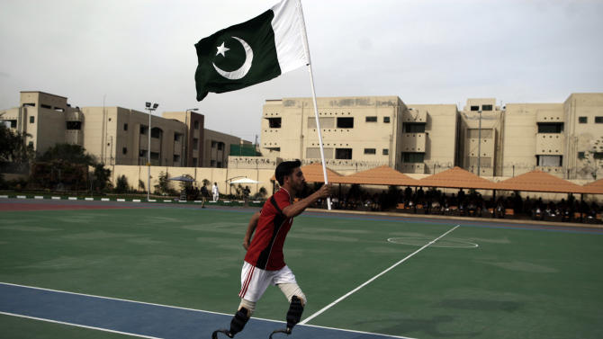 A disabled Pakistani soldier runs while carrying his national flag during a sports competition, in Rawalpindi, Pakistan, Saturday, March 16, 2013. Dozens of wounded Pakistani troops, many of them maimed during the fighting in the country's tribal areas bordering Afghanistan, gathered Saturday for a sports competition designed to help them recover -- in body and spirit. (AP Photo/Muhammed Muheisen)