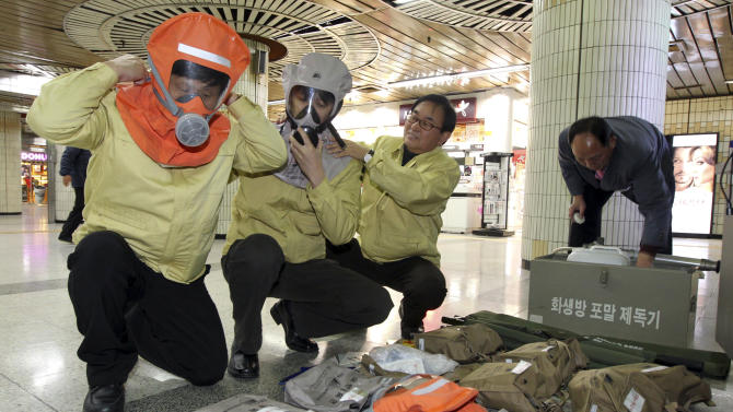Members of the National Emergency Management Agency check their gas masks as they inspect emergency evacuation facilities at a subway station in Seoul, South Korea, Sunday, Nov. 28, 2010. South Korea, Sunday, Nov. 28, 2010. The rattle of new artillery fire from North Korea just hours after the U.S. and South Korea launched a round of war games in Korean waters sent residents, journalists, police and troops on a front-line island scrambling for cover Sunday. (AP Photo/Yonhap, Kim Ju-sung )  KOREA OUT
