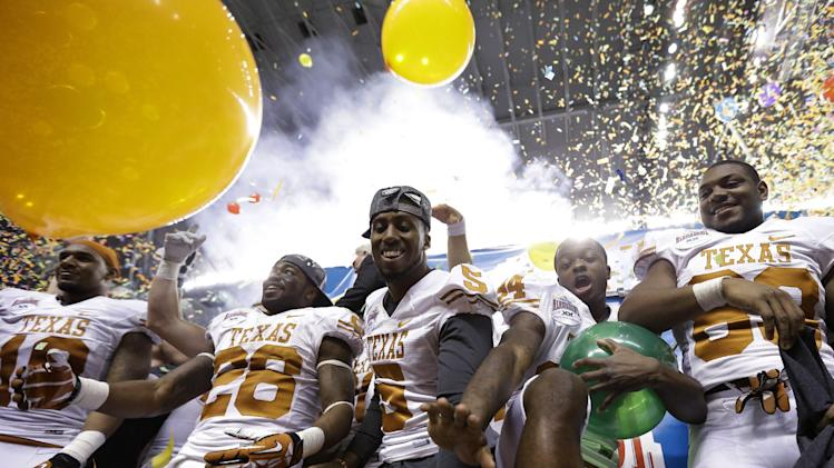 Texas' Marquise Goodwin, second from right, celebrates with teammates after defeating Oregon State in the Alamo Bowl NCAA football game, Saturday, Dec. 29, 2012, in San Antonio.  Texas won 31-27. (AP Photo/Eric Gay)