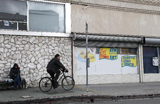A man rides a bicycle in the downtown area of Stockton, Calif., Wednesday, Feb. 29, 2012. A red, white and blue sign declaring Stockton an ìAll-America Cityî still adorns City Hall, but the buildingís crumbling facade tells the real story of the communityís recent fortunes. Since the sign went up nearly a decade ago, Stockton has twice topped Forbes magazineís list of ìAmericaís most miserable cities.î And now another unflattering title could be headed its way: largest American city to declare bankruptcy. (AP Photo/Ben Margot)