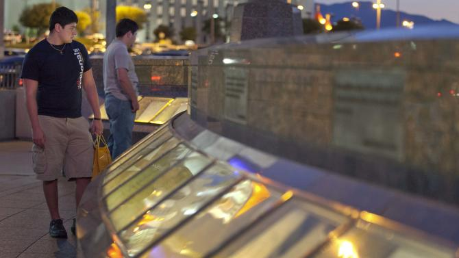 "In this June 22, 2011 photo, Victor, left, and Ben Ortega, brothers from El Paso, Texas, walk along the September 11 memorial outside the New York, New York Hotel and Casino, in Las Vegas. Across the country, an extravagant ritual of public grief for ""our losses"" has not abated in a decade, from public memorials of steel and photos to the palpable sadness of strangers. Experts say Americans are still processing the most tragic public event of their lifetimes, before they can begin to let go. (AP Photo/Julie Jacobson)"