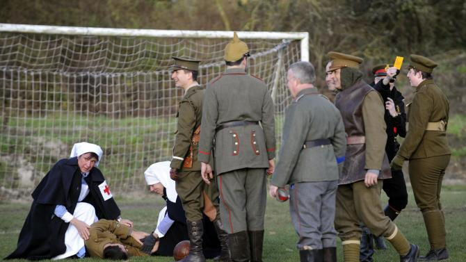 Figurants play a soccer match to mark the centenary of the legendary football match between the German and Allied troops on the Western Front during the Christmas Truce of 1914, at the Flanders Peace Field in Mesen