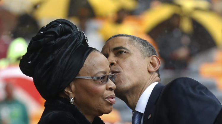 President Barrack Obama kisses Nelson Mandela's widow Graca Machel during the memorial service for former South African president Nelson Mandela at the FNB Stadium in Soweto near Johannesburg, Tuesday, Dec. 10, 2013. (AP Photo/Matt Dunham)