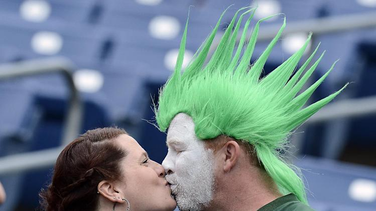 New York Jets fans Ana Hall and Rick Martin kiss as they watch players warm up before an NFL football game between the Jets and the Tennessee Titans on Sunday, Sept. 29, 2013, in Nashville, Tenn