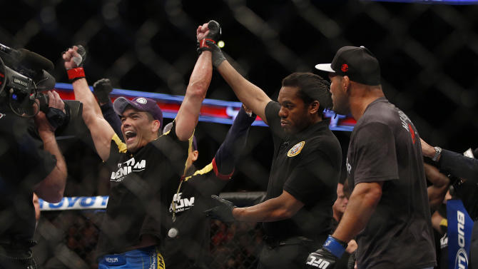 Lyoto Machida, left, of Brazil, celebrates his split decision win against Dan Henderson, right, after their UFC 157 light heavyweight mixed martial arts match in Anaheim, Calif., Saturday, Feb. 23, 2013. (AP Photo/Jae C. Hong)