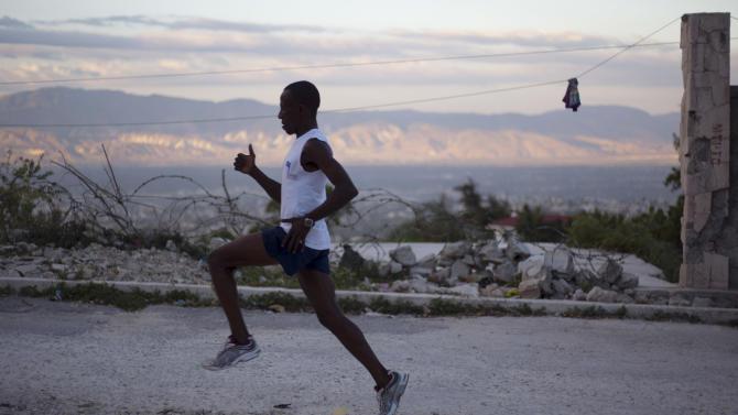 """FILE - In this Jan. 7, 2013 file photo, Astrel Clovis, a 42-year-old marathon runner, trains in the early morning in Petionville, a suburb of Port-au-Prince, Haiti.  Six days a week, Clovis sets off at daybreak and has been running the hills and streets of Port-au-Prince for the past 10 years. He decided to take the sport seriously after he entered a race in downtown Port-au-Prince on a whim - and won. Clovis' story inspired the J/P Haitian Relief Organization to sponsor five Haitian runners so they can compete in the New York City Marathon in November 2013.  Sean Penn's relief organization will accept the top three men and two women finishers in a rare half-marathon that will wind through the Haitian capital of Port-au-Prince on Sunday, June 1, 2013. """"This is my dream _ to participate in a marathon, out in the world,"""" Clovis said. """"I'm very excited to represented Haiti in the New York marathon, if I qualify."""" (AP Photo/Dieu Nalio Chery, File)"""
