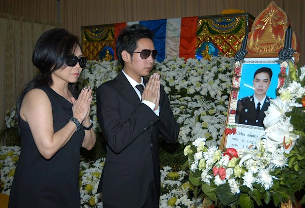 In this photo taken Wednesday, Sept. 5, 2012, Vorayuth Yoovidhaya, right, and mother Daranee, pay last respects in front of the coffin of Sgt. Wichian Klinprasert, a police officer who was killed in a