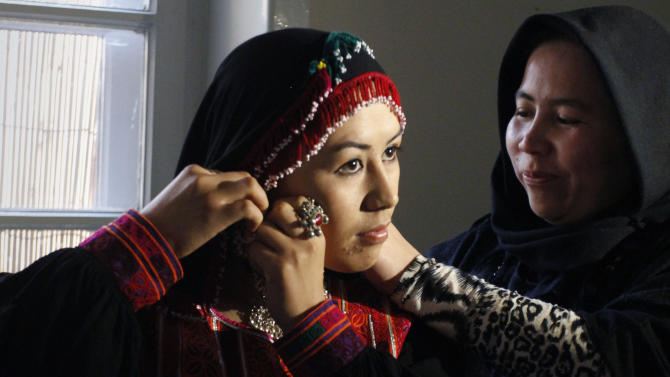 An Afghan model prepares prior a fashion show in Kabul, Afghanistan, Friday, Feb. 8, 2013. The rare fashion show in this war-weary capital was a small production but a big idea — part of an Afghan group's efforts to empower women by breaking down barriers in this highly conservative Muslim society. (AP Photo/Musadeq Sadeq)