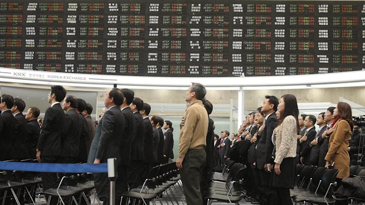 CORRECTS THE DATE - Staff members of the Korea Stock Exchange Market salute to the national flag during the opening ceremony to commence the Year 2013 trading at the Seoul Stock Exchange Wednesday, Jan. 2, 2013. The benchmark Korea Composite Stock Price Index (KOSPI) started up 16.69 points, or 0.84 percent, at 2, 013.74.(AP Photo/Ahn Young-joon)