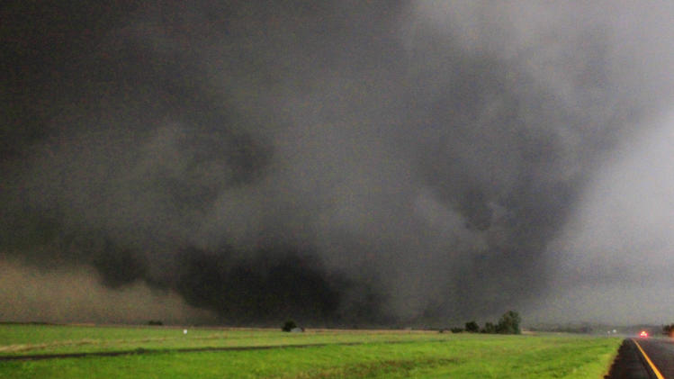 FILE - In this May 24, 2011 file photo, a half-mile-wide tornado moves towards Piedmont, Okla. In 2011 the United States saw one of the busiest tornado seasons in generations: Nearly 1,700 tornadoes that killed 553 people. With the planet heating up, many scientists seem fairly certain some weather elements like hurricanes and droughts will worsen. But as the traditional season nears, scientists are still trying to figure out if there be more or fewer tornadoes as global warming increases. (AP Photo/The Oklahoman, Paul Southerland, File)