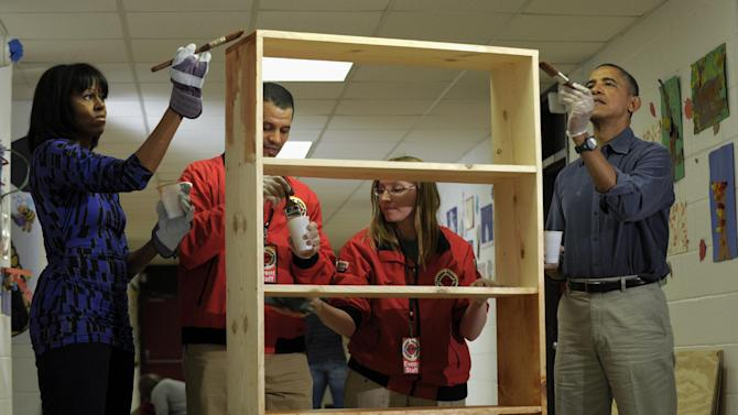 President Barack Obama and first lady Michelle Obama stain a bookshelf at Burrville Elementary School in Washington, Saturday, Jan. 19, 2013, as the the first family participated in a community service project for the National Day of Service, part of the 57th Presidential Inauguration. (AP Photo/Susan Walsh)