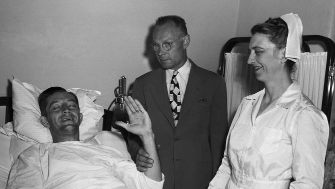 """FILE - In this June 17, 1949 file photo, Philadelphia Phillies first baseman Eddie Waitkus smiles from his bed in Illinois Masonic Hospital in Chicago as his father, Stephen, holds up his arm for an attempted wave. Waitkus was shot and seriously wounded June 14 in a Chicago hotel by 19-year-old Ruth Steinhagen. Steinhagen died of natural causes at 83 in late December 2012. Her death is the final chapter in one of the most sensational and bizarre criminal cases in Chicago history that made headlines around the country. She was the inspiration for Bernard Malamud's novel """"The Natural"""" and the 1984 movie starring Robert Redford. (AP Photo/File)"""