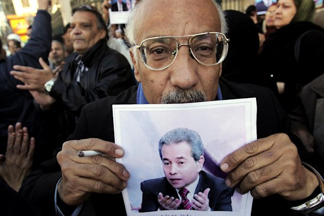A supporter of Tawfiq Okasha, a popular Egyptian TV presenter, kisses his poster at the Cairo South court in Cairo, Egypt, Tuesday, Jan. 8, 2013. An Egyptian court acquitted Okasha on charges of incit