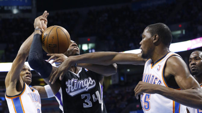 Oklahoma City Thunder forward Kevin Durant (35) knocks the ball away from Sacramento Kings forward Jason Thompson (34) in front of teammate guard Russell Westbrook (0) during the second quarter of an NBA basketball game in Oklahoma City, Friday, Dec. 14, 2012. (AP Photo/Sue Ogrocki)