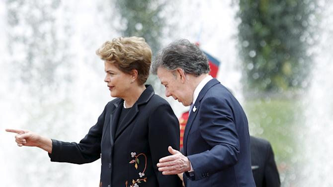 Brazil's President Dilma Rousseff talks to Colombia's President Juan Manuel Santos during a review of honour guard at the Narino Palace in Bogota