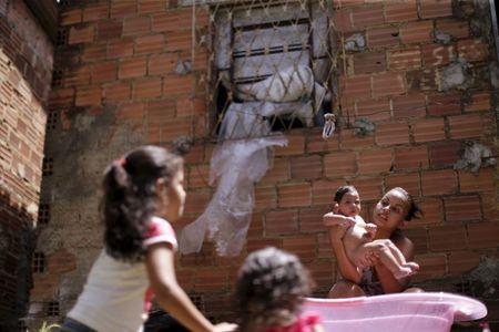 Rosana Vieira Alves bathes her 4-month-old daughter Luana Vieira, who was born with microcephaly, as her daughters play outside their home in Olinda
