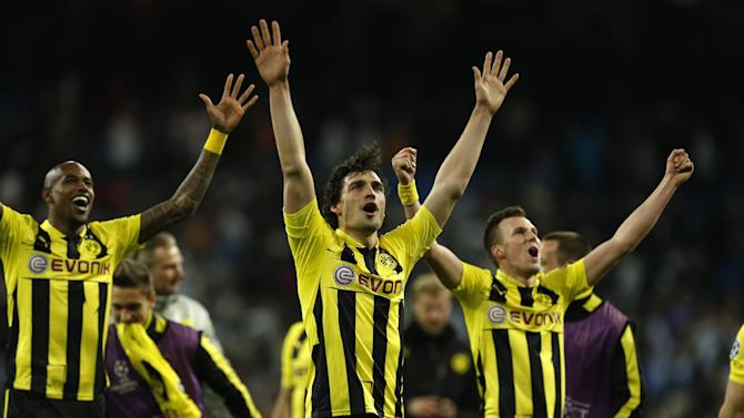 Dortmund players Felipe Santana, left, and Mats Hummels celebrate advancing to the final after the Champions League semifinal second leg soccer match between Real Madrid and Borussia Dortmund at the Santiago Bernabeu stadium in Madrid, Spain, Tuesday, April 30, 2013. (AP Photo/Andres Kudacki)