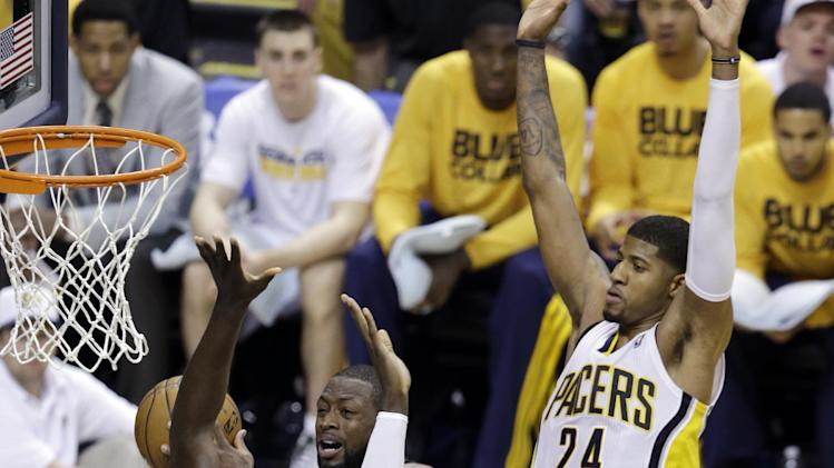 Miami Heat's Dwyane Wade (3) goes makes a pass against Indiana Pacers' Roy Hibbert (55) and Paul George during the second half of Game 3 of the NBA Eastern Conference basketball finals in Indianapolis, Sunday, May 26, 2013. (AP Photo/Michael Conroy)