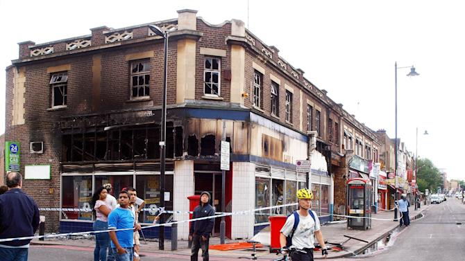 A burned out building, which was destroyed during rioting and looting on the Tottenham High Road in north London over the weekend ,  is seen Monday Aug. 8 2011.  Residents surveyed shattered streets and arrested more suspects Monday after riots and looting erupted in an impoverished London neighborhood and hopscotched across the city that hosts next summer's Olympic Games. (AP Photo/ Max Nash / PA )  UNITED KINGDOM OUT