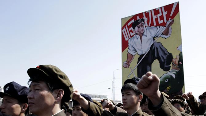 """North Koreans punch the air during a rally at Kim Il Sung Square in downtown Pyongyang, North Korea, Friday, March 29, 2013. Tens of thousands of North Koreans turned out for the mass rally at the main square in Pyongyang in support of their leader Kim Jong Un's call to arms. The placard reads: """"U.S. forces, get out!"""" (AP Photo/Jon Chol Jin)"""