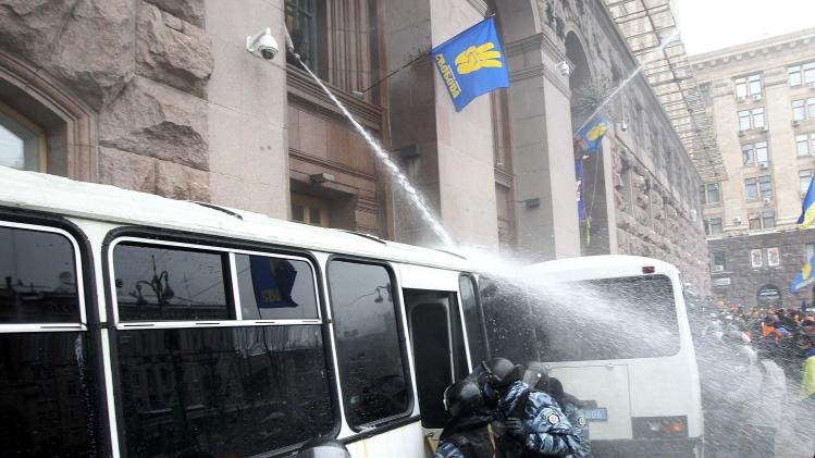 Protesters spray riot police with water hose to prevent it from entering the City Hall in Kiev