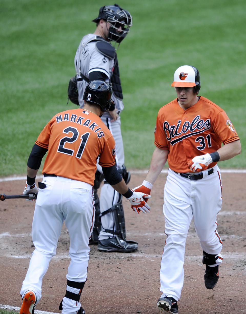 Baltimore Orioles' Taylor Teagarden (31) celebrates his home run with teammate Nick Markakis (21) as Chicago White Sox catcher A.J. Pierzynski looks on during the third inning of a baseball game, Thursday, Aug. 30, 2012, in Baltimore. (AP Photo/Nick Wass)