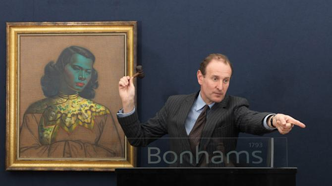 """In this hand out photo supplied by Bonham's Auctioneers Giles Peppiatti takes bids for Vladimir Tretchikoff's painting titled """"Chinese Girl"""" at the Bonham's Auctions in London Wednesday, March 20, 2013. The iconic painting, said to be one of the most reproduced in the world, is coming home to South Africa after more than half a century in a private Chicago collection, Bonhams auction house announced Thursday, March 21, 2013 after a record sale. The picture sold Wednesday for 982,050 British pounds (nearly $1.5 million) — double the expected price and a record for Tretchikoff or any South African artist, according to Giles Peppiatt, director of South African art at Bonhams. (AP Photo/Bonham's-Giles Peppiatti-HO)"""